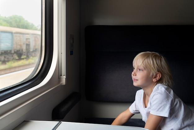 Menino se senta em um vagão de compartimento e olha pela janela. viaje de trem.
