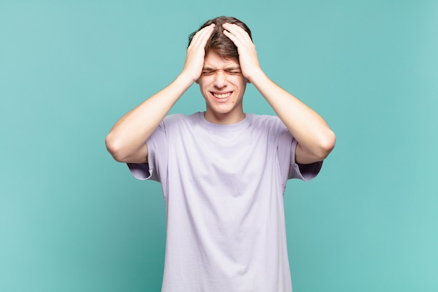 Menino se sentindo estressado e ansioso, deprimido e frustrado com uma dor de cabeça, levando as duas mãos à cabeça