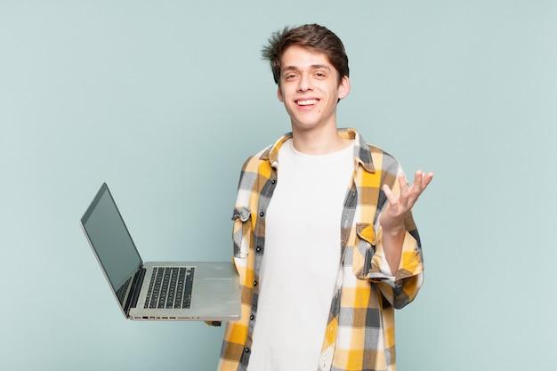 Menino se sentindo feliz, surpreso e alegre, sorrindo com atitude positiva, percebendo uma solução ou ideia. conceito de laptop
