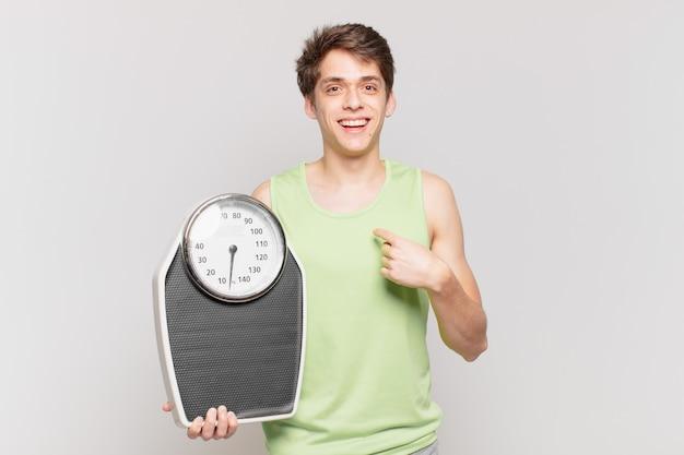 Menino se sentindo feliz, surpreso e orgulhoso, apontando para si mesmo com um conceito de escala de olhar surpreso e animado