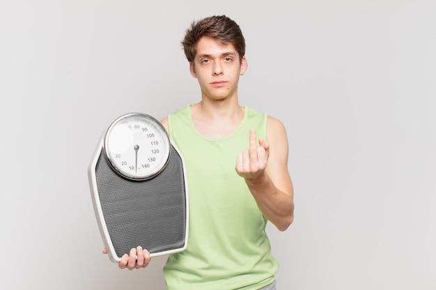 Menino se sentindo irritado, irritado, rebelde e agressivo, sacudindo o dedo médio, lutando contra o conceito de escala