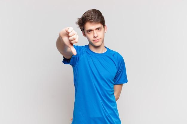 Menino se sentindo zangado, irritado, irritado, desapontado ou descontente, mostrando o polegar para baixo com um olhar sério