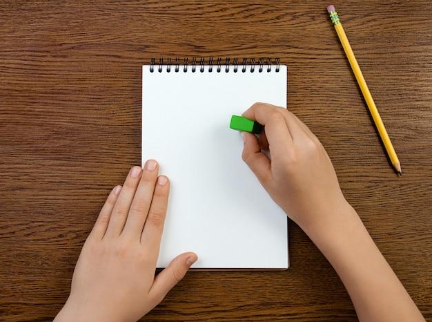 Menino segura a borracha e apaga em um caderno branco em branco