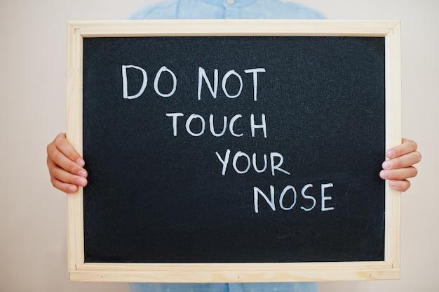 Menino segura inscrição na lousa com o texto não toque no nariz