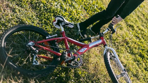Menino segurando a bicicleta na grama