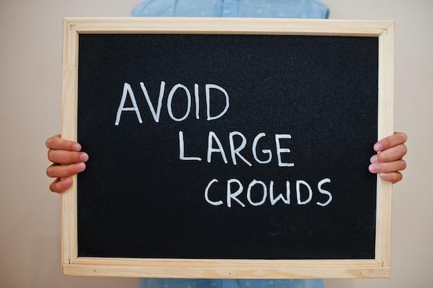 Menino segurando a inscrição no quadro para evitar grandes multidões