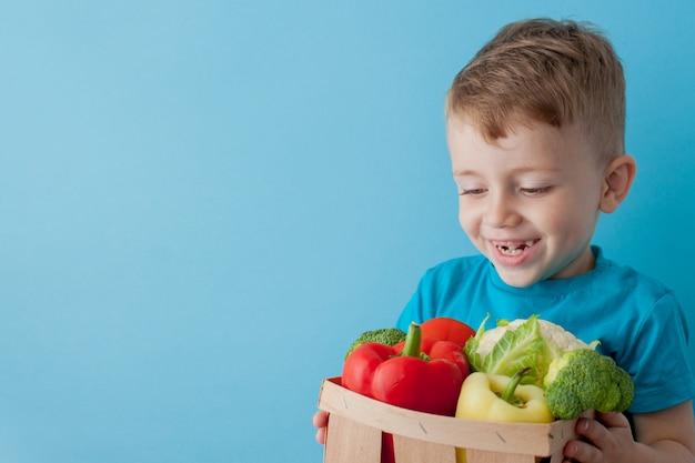 Menino segurando cesta com legumes frescos em fundo azul. conceito vegano e saudável.