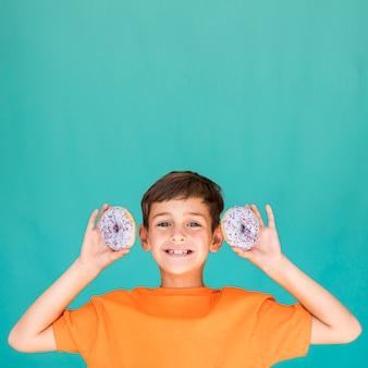 Menino, segurando, dois, donuts, com, espaço cópia