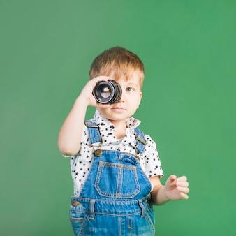 Menino, segurando, lente câmera, em, olho