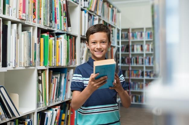 Menino, segurando o livro na biblioteca da escola