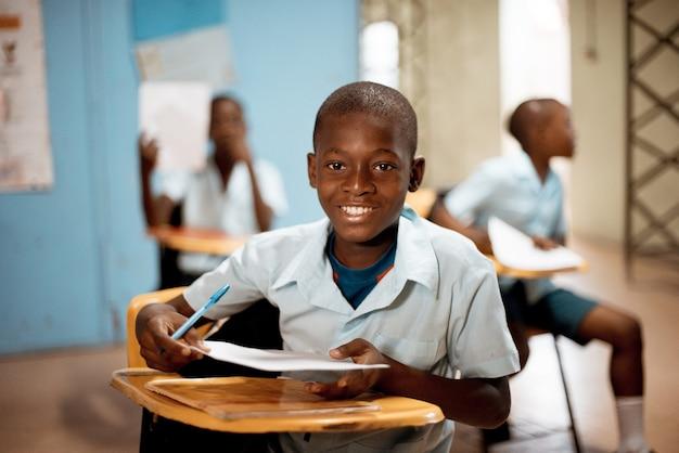 Menino segurando papel branco na escola