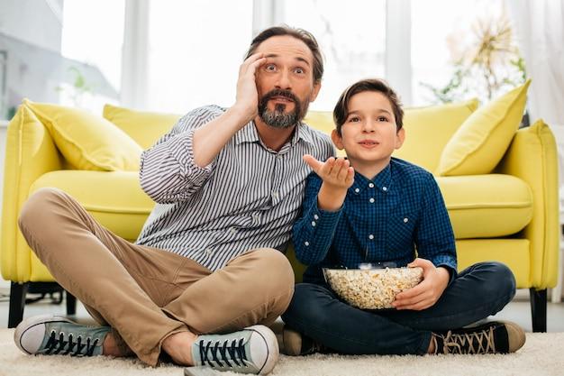 Menino segurando pipoca e seu pai parecendo impressionado enquanto está sentado no chão assistindo a um jogo incrível na tv