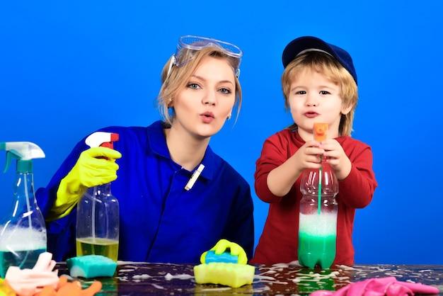 Menino segurando spray na mesa, criança sentada à mesa de madeira com atividades de limpeza de produtos de limpeza