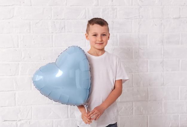 Menino segurando um balão em forma de coração azul na superfície branca