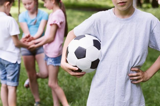 Menino, segurando, um, bola futebol