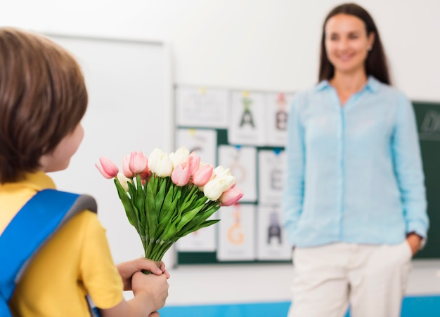 Menino segurando um buquê de flores para a professora