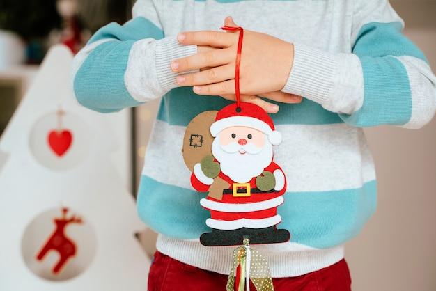 Menino segurando um enfeite de papai noel para decoração de natal