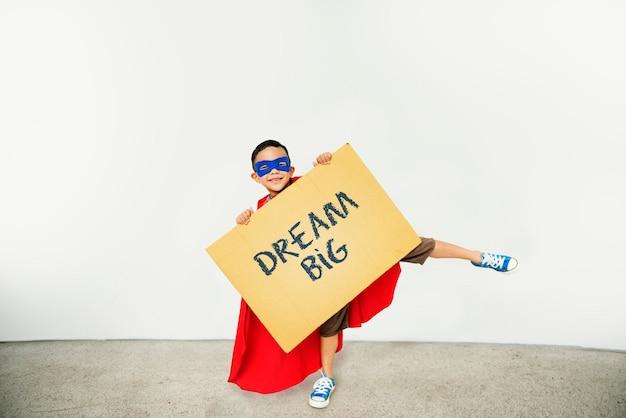 Menino segurando um sinal com dream big