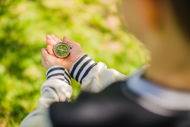 Menino segurando uma bússola no parque