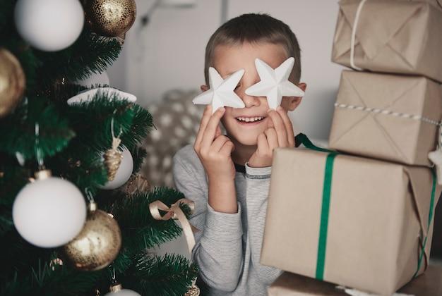 Menino segurando uma decoração de natal na frente dos olhos