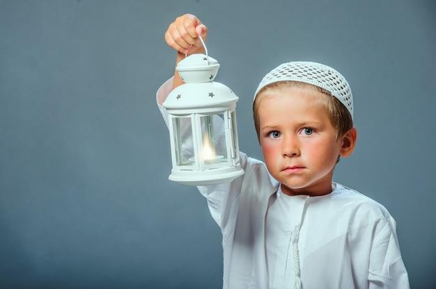 Menino segurando uma lanterna do ramadã