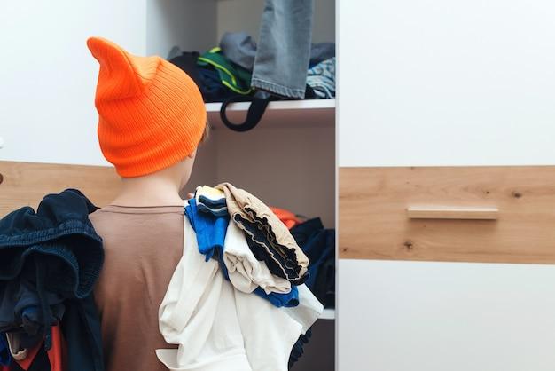 Menino segurando uma pilha de roupas sujas. quarto de criança em casa bagunçado. tarefas domésticas tarefas domésticas.