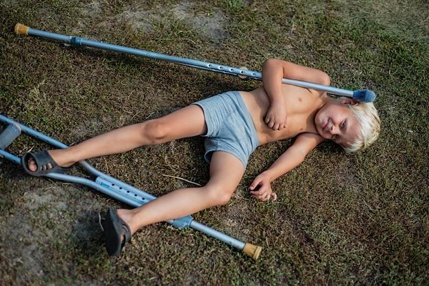 Menino sem camisa, com suas muletas, caiu no chão