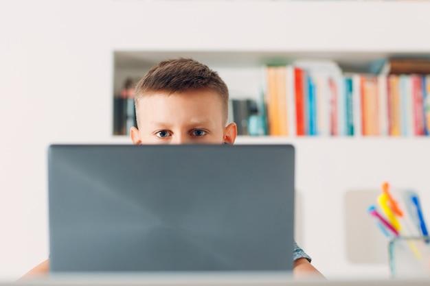 Menino sentado à mesa com um laptop e se preparando para a escola