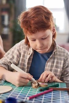 Menino sentado à mesa decorando artesanato com giz de cera durante a aula de arte