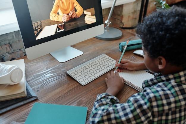 Menino sentado à mesa em frente ao monitor do computador durante a aula online, ouvindo o professor na tela e fazendo anotações no caderno