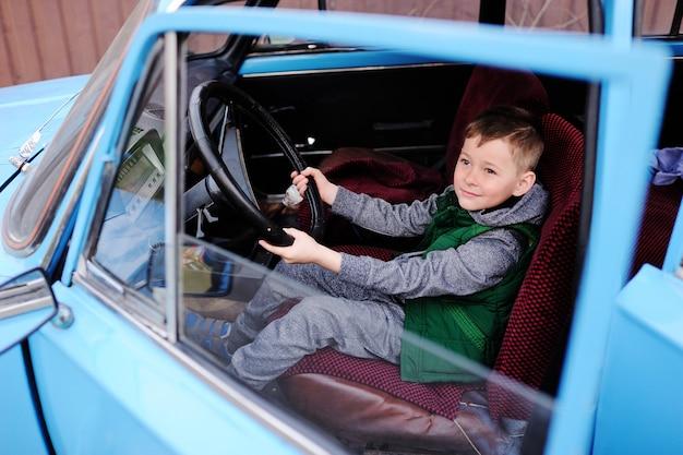 Menino sentado ao volante de um carro retrô azul