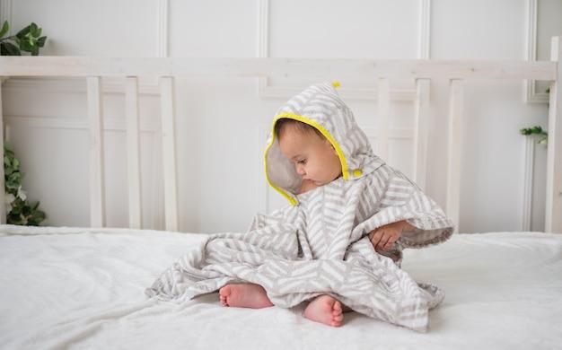 Menino sentado de lado em uma toalha de banho com capuz em uma cama branca