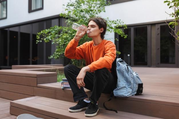 Menino sentado e bebendo água com uma mochila grande perto do pátio da universidade