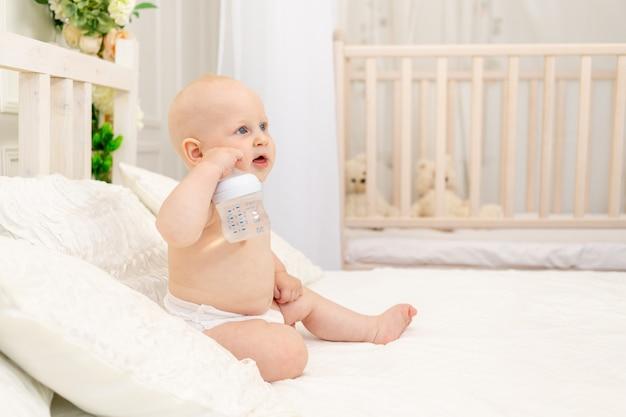 Menino sentado em fraldas em uma cama branca