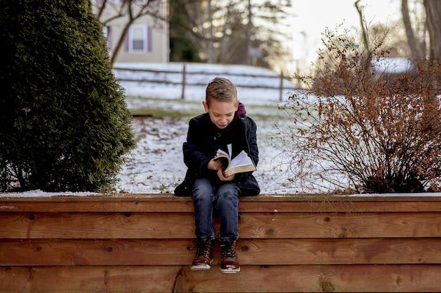 Menino sentado em pranchas de madeira e lendo a bíblia em um jardim coberto de neve