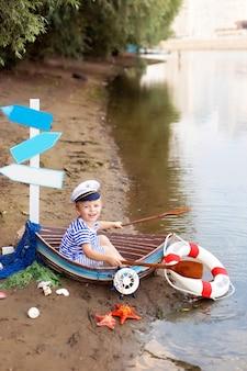 Menino sentado em um barco na praia