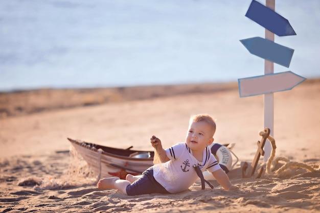 Menino sentado em um barco, vestido de marinheiro, em uma praia com conchas à beira-mar