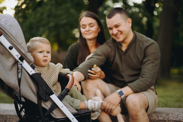 Menino sentado em um carrinho de criança com os pais no fundo sentado na balaustrada de pedra looki