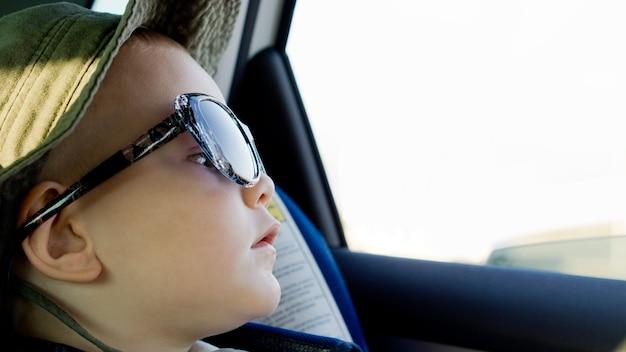 Menino sentado em um carro com um chapéu de sol e óculos de sol enormes