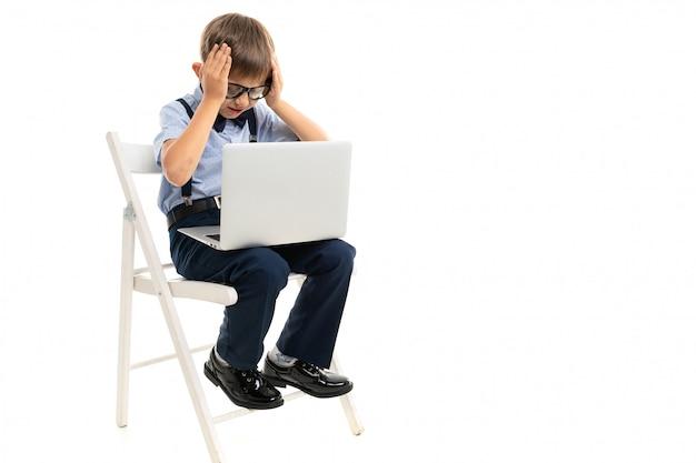 Menino sentado em uma cadeira e segurando sua cabeça enquanto segura um laptop no colo em uma parede branca
