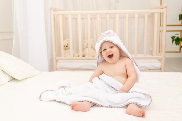 Menino sentado em uma cama branca com uma toalha branca