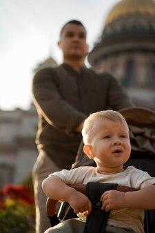 Menino sentado em uma carruagem, seu pai o está carregando. imagem com foco seletivo. foto de alta qualidade
