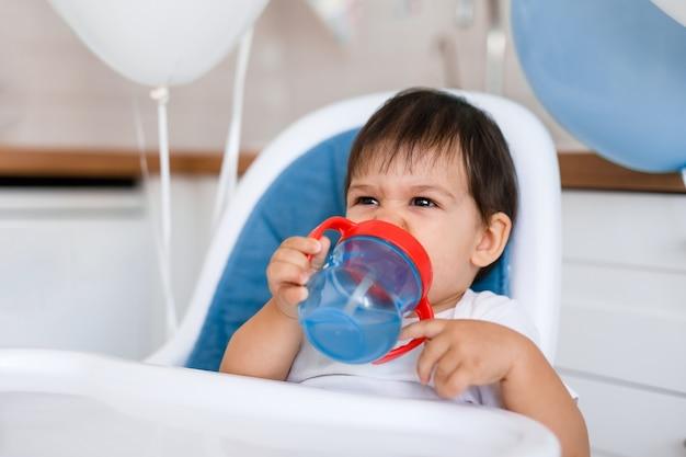 Menino sentado na cadeira alta azul em casa na cozinha branca e bebendo água do copo com canudinho no fundo com balões.