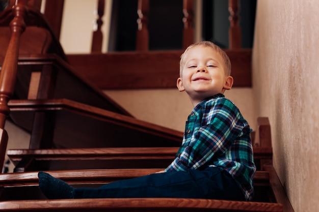 Menino sentado na escada em casa