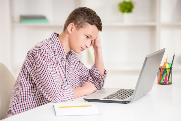 Menino sentado na mesa com o laptop e fazendo lição de casa.