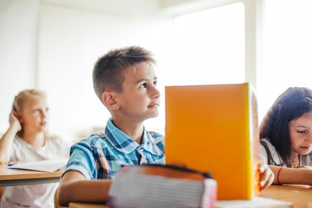 Menino sentado na mesa da escola, segurando o livro de texto