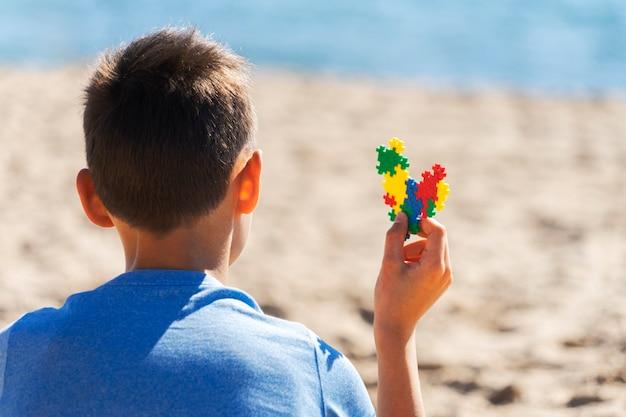 Menino sentado na praia, olhando para o mar, oceano e segurando um coração colorido de consciência de autismo.