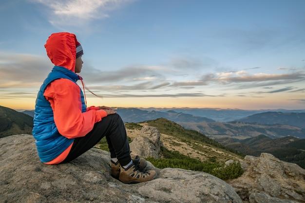Menino sentado nas montanhas, apreciando a vista incrível da paisagem montanhosa