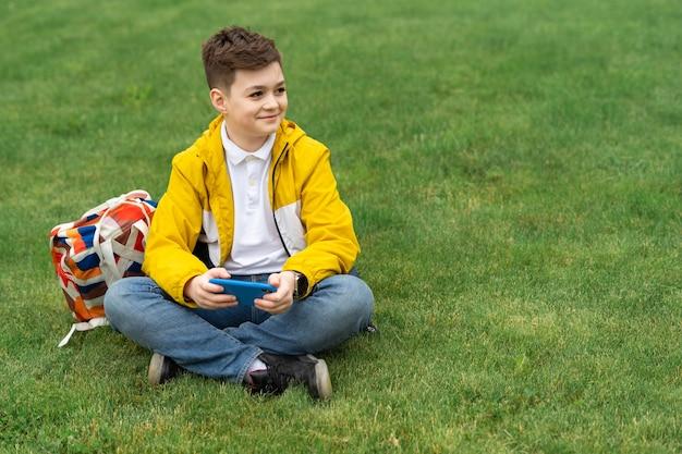 Menino sentado no gramado com um smartphone