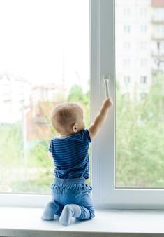 Menino sentado no parapeito da janela tentando abri-la puxando a maçaneta